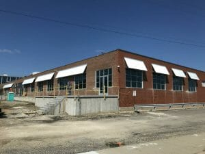 Commercial building with many custom corrugated sheet metal awnings