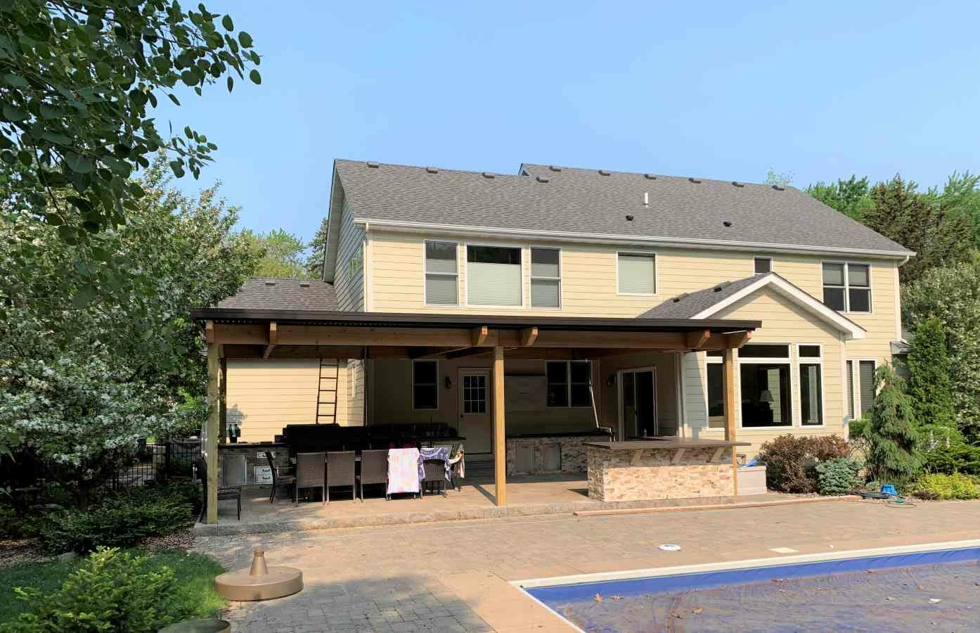 Residential patio with covered roof using motorized louvered product by Acme Awning.